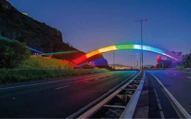 Photograph of a bridge at night lit up with neon rainbow coloured lights
